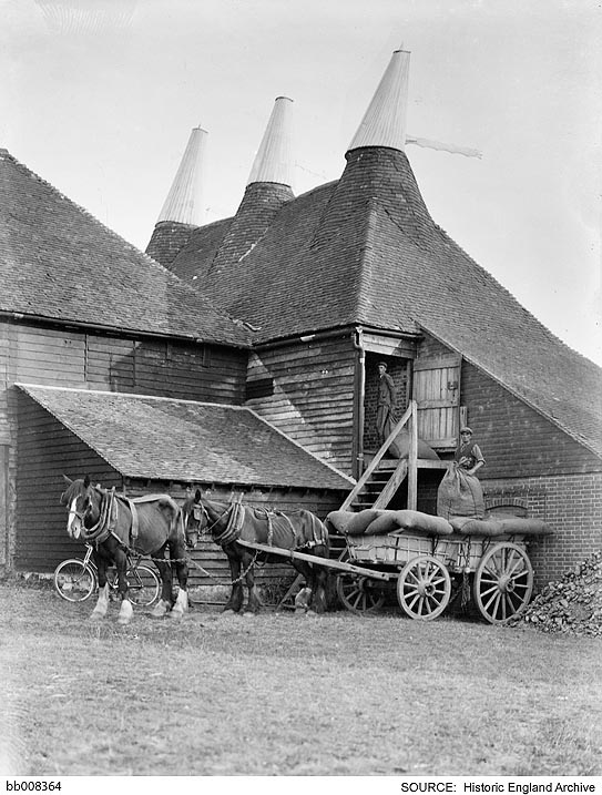 exterior view showing sacks being unloaded from cart 1933 great dixter oast house east sussex rother northiam